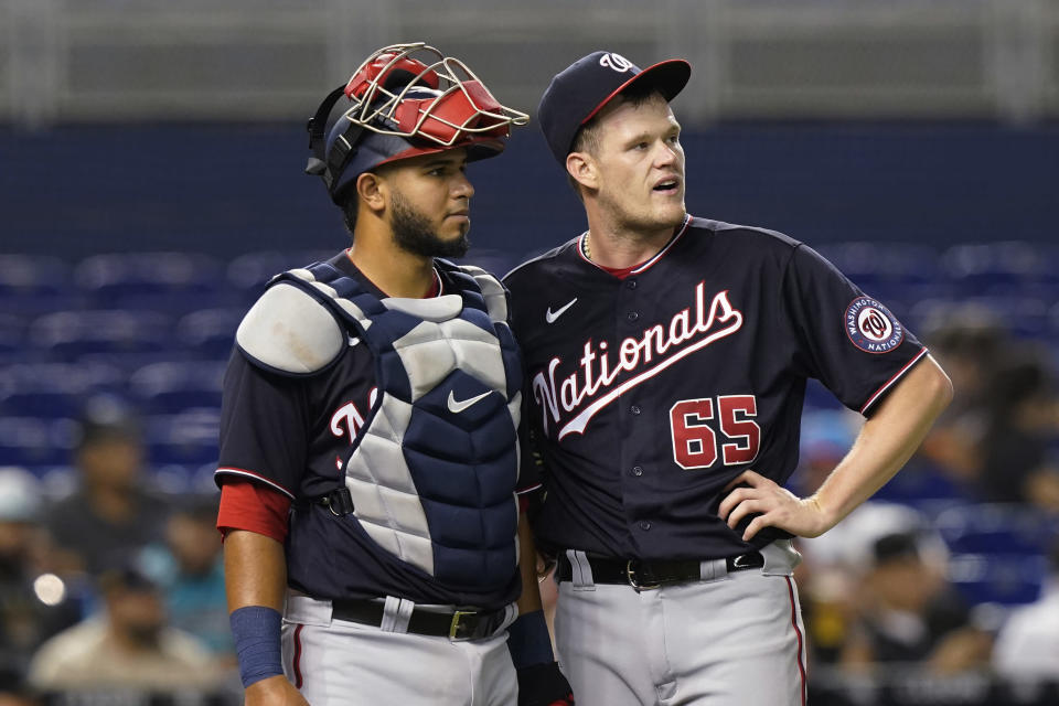Washington Nationals' catcher Keibert Ruiz and pitcher Josh Rogers (65) watch the replay of a hit by Miami Marlins' Miguel Rojas during the third inning of a baseball game against the Miami Marlins, Tuesday, Sept. 21, 2021, in Miami. (AP Photo/Marta Lavandier)