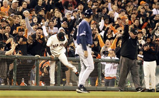 Fans cheer San Francisco Giants third baseman Pablo Sandoval, center left, as he climbs over the fence in third base foul territory after making a catch on a ball hit by San Diego Padres' Yonder Alonso in the fourth inning of a baseball game, Saturday, Sept 22, 2012, in San Francisco. (AP Photo/Ben Margot)