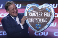 """FILE - In this Friday, Sept. 24, 2021 file photo, Christian Democrats chancellor candidate Armin Laschet lifts a gingerbread heart reading """"Chancellor for Germany"""" during a election campaign event in Munich, Germany. Germany's closely fought election on Sunday will set the direction of the European Union's most populous country after 16 years under Angela Merkel, whose party is scrambling to avoid defeat by its center-left rivals after a rollercoaster campaign. (AP Photo/Matthias Schrader, File)"""