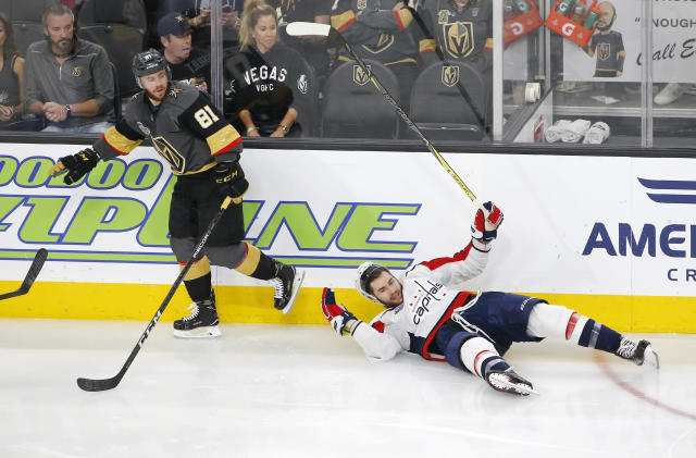 Washington Capitals right wing Tom Wilson, right, falls to the ice after being checked by Vegas Golden Knights center Jonathan Marchessault during the third period in Game 2 of the NHL hockey Stanley Cup Finals on Wednesday, May 30, 2018, in Las Vegas. (AP Photo/Ross D. Franklin)