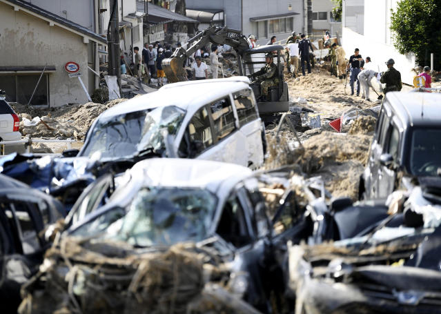 <p>Cars are trapped in mud as residents clean up after days of heavy rain hit southwestern Japan, in Hiroshima city, southwestern Japan, Tuesday, July 10, 2018. (Photo: Ryosuke Ozawa/Kyodo News via AP) </p>