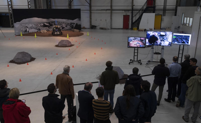 Guests and media watch as astronaut Luca Parmitano of Italy, seen on screen, remote controls the Space Rover, rear, which successfully picked up a rock during a training exercise of the European Space Agency, ESA, in Katwijk, near The Hague, Netherlands, Monday, Nov. 25, 2019. (AP Photo/Peter Dejong)