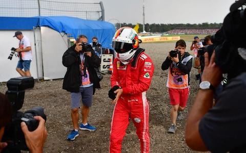 Ferrari's German driver Sebastian Vettel walks to the pits after he was forced to abandon during the German Formula One Grand Prix at the Hockenheim racing circuit on July 22, 2018 in Hockenheim, southern Germany - Credit: afp