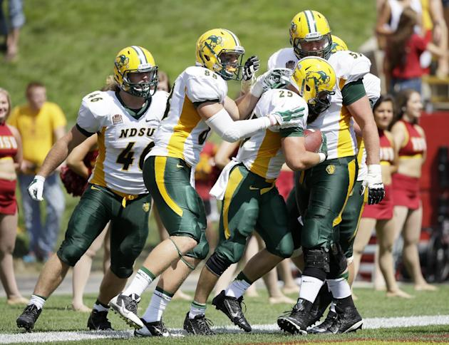 North Dakota State running back Chase Morlock (25) celebrates with teammates after scoring on a 66-yard touchdown run during the second half of an NCAA college football game against Iowa State, Saturday, Aug. 30, 2014, in Ames, Iowa. North Dakota State won 34-14. (AP Photo/Charlie Neibergall)