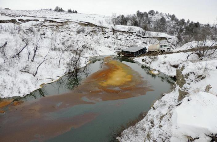 FILE - This Dec. 10, 2016, file photo, provided by the North Dakota Department of Health shows an oil spill from the Belle Fourche Pipeline that was discovered Dec. 5, 2016 in Ash Coulee Creek, a tributary of the Little Missouri River, near Belfield, N.D. President Barack Obama's administration has scaled back new safety measures for the sprawling network of fuel pipelines that crisscross the United States after complaints from industry over the potential cost. The administration on Friday, Jan. 13, 2017, finalized new regulations for almost 200,000 miles of pipelines that transport crude oil, gasoline and other hazardous liquids. A proposed requirement for companies to immediately repair problems discovered on their lines was dropped. (Scott Stockdill/North Dakota Department of Health via AP, File)