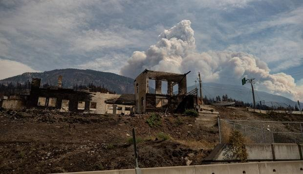 A property destroyed by the Lytton Creek wildfire is seen as a pyrocumulus cloud, also known as a fire cloud, produced by the same fire rises in the mountains above Lytton, B.C., on Sunday.  (The Canadian Press/Darryl Dyck - image credit)