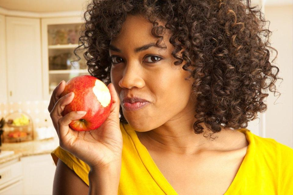 woman eating fresh red apple inside house kitchen