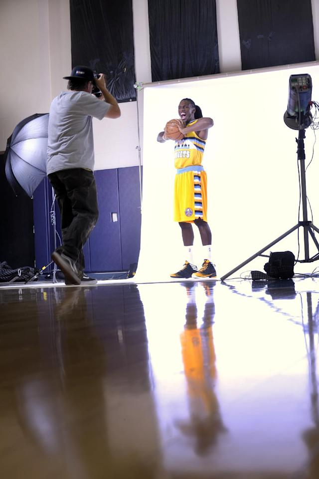 Photographer Garrett Ellwood shoots a photo of Kenneth Faried during Denver Nuggets NBA basketball media day on Monday, Sept. 30, 2013, in Denver. (AP Photo/Jack Dempsey