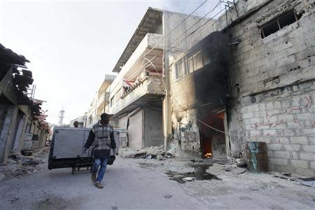 People loot furniture after soldiers loyal to Syria's President Bashar al-Assad took control of Hujaira town from rebel fighters, in the town south of Damascus November 21, 2013. REUTERS/Alaa Al-Marjani
