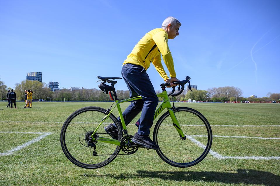 <p>Sadiq Khan performs a bunny hop on a borrowed bike in Hackney Marshes</p> (Getty Images)