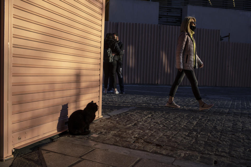 A woman wearing a protective face mask walks as a young couple kiss each other in central Athens, on Wednesday, March 3, 2021. Greek health authorities have reported an abrupt spike in new confirmed COVID-19 infections, about half of which were in the greater Athens region, despite an ongoing lockdown. (AP Photo/Petros Giannakouris)