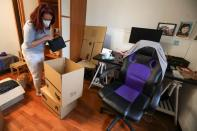 Ines Alcolea places objects inside moving boxes before leaving her rented apartment in Madrid