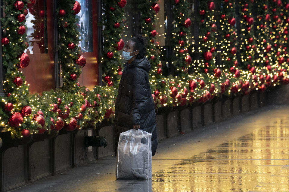 A shopper looks at Macy's window displays, Monday, Nov. 30, 2020, in New York. (AP Photo/Mark Lennihan)