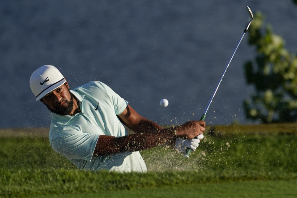 Tony Finau hits out of a bunker on the 18th green in the final round at The Northern Trust golf tournament at Liberty National Golf Course Monday, Aug. 23, 2021, in Jersey City, N.J. (AP Photo/John Minchillo)