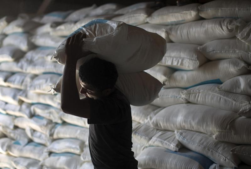 A Palestinian man carries bags of flour he received at a distribution centre of the United Nations Relief and Works Agency in Gaza City on August 11, 2014 (AFP Photo/Mahmud Hams)