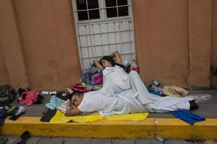 A migrant woman slowly begins to wake after sleeping on a sidewalk in Tapanatepec, Mexico, Sunday, Oct. 28, 2018. Thousands of migrants who are part of a caravan of Central Americans trying to reach the U.S. border took a break Sunday on their long journey toward the U.S. border. (AP Photo/Rodrigo Abd)