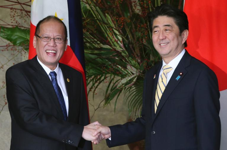 Japanese Prime Minister Shinzo Abe (R) greets Philippines' President Benigno Aquino the Abe's official residence in Tokyo, on December 13, 2013