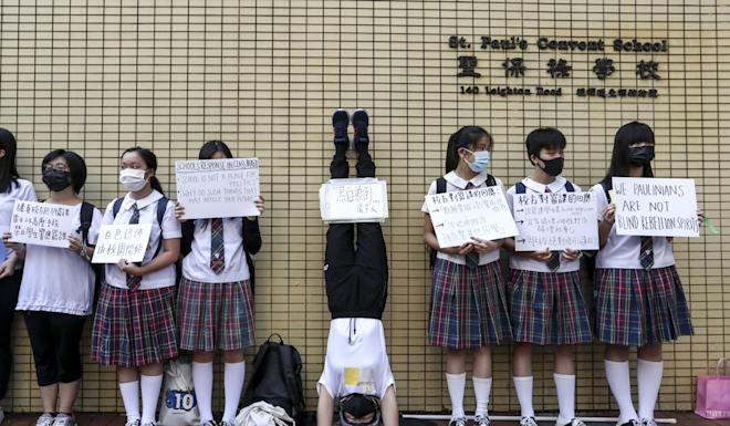 Students of St. Paul's Convent School protest outside the campus in Causeway Bay, and hold signs criticising the school's principal for stopping an earlier one. Photo: Jonathan Wong