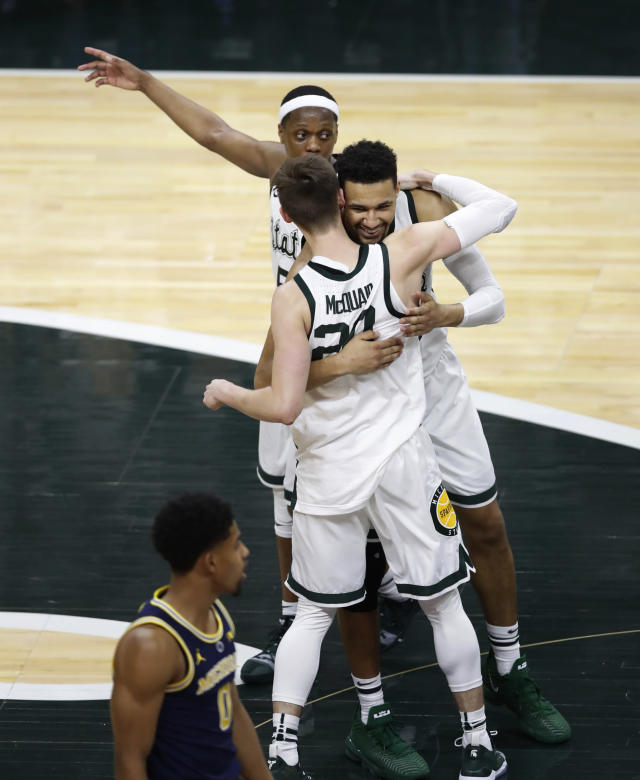 Michigan State forward Kenny Goins hugs guard Matt McQuaid (20) next to Michigan guard David DeJulius (0) at the end of an NCAA college basketball game Saturday, March 9, 2019, in East Lansing, Mich. Michigan State won 75-63 to share the Big Ten title with Purdue. (AP Photo/Carlos Osorio)