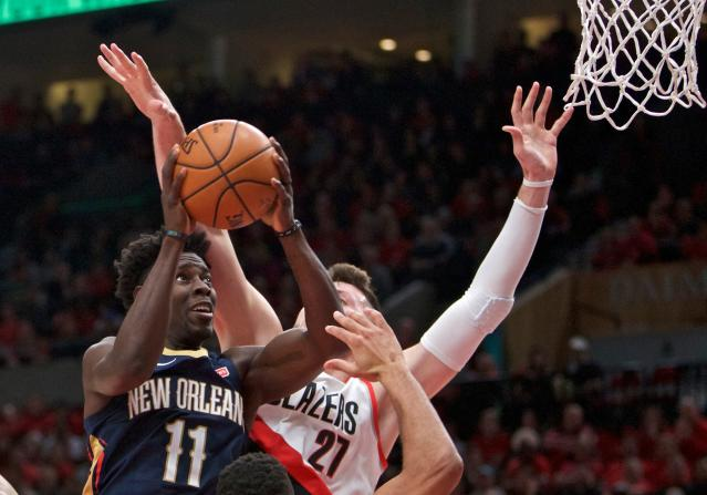 Pelicans guard Jrue Holiday, left, shoots next to Trail Blazers center Jusuf Nurkic during the first half of Game 2 Tuesday night. (AP)