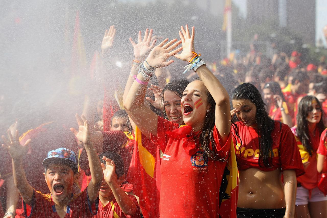 MADRID, SPAIN - JULY 02:  Supporters of Spain's national football team are hosed down by a fireman before congratulating their team's players on their return to Madrid following their victory in Euro 2012 football championships on July 2, 2012 in Madrid, Spain. Spain beat Italy 4-0 in the UEFA EURO 2012 final match in Kiev, Ukraine, on July 1, 2012.  (Photo by Oli Scarff/Getty Images)