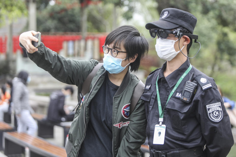 HANGZHOU, CHINA - MARCH 24 2020: A tourist selfies with a security guard wearing an augmented reality (AR) eyewear equipped with an infrared temperature detector in Xixi Wetland Park in Hangzhou in east China's Zhejiang province Tuesday, March 24, 2020. The eyewear will alert the guard when it detects someone with fever signs, the latest weapon in the fight against the COVID-19.- PHOTOGRAPH BY Feature China / Barcroft Studios / Future Publishing (Photo credit should read Feature China/Barcroft Media via Getty Images)
