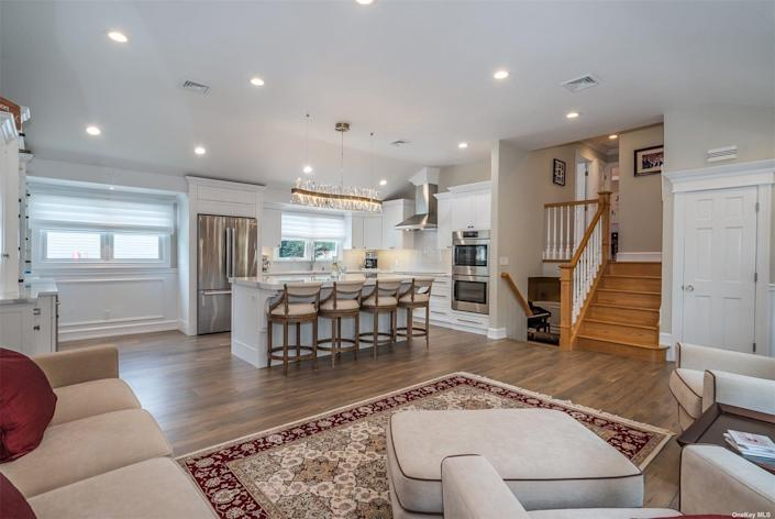 The open floor plan with a kitchen, family room down the steps, and a bedroom up the stairs