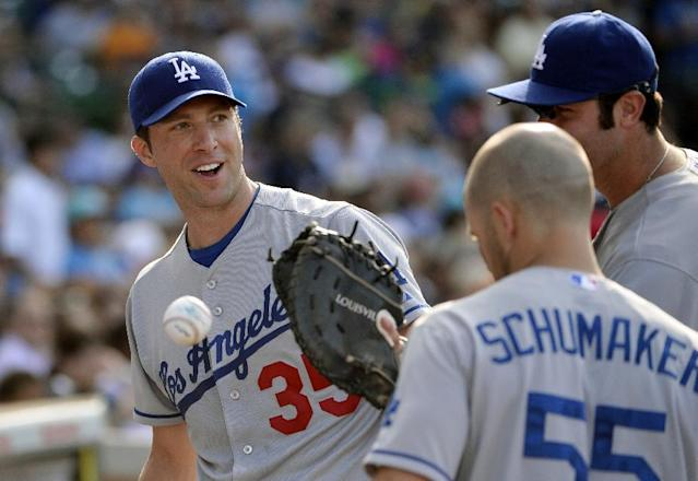Los Angeles Dodgers starting pitcher Chris Capuano, left, smiles as he walks back to the dugout with his teammates after the sixth inning of a baseball game against the Chicago Cubs, Saturday, Aug. 3, 2013, in Chicago. (AP Photo/Brian Kersey)