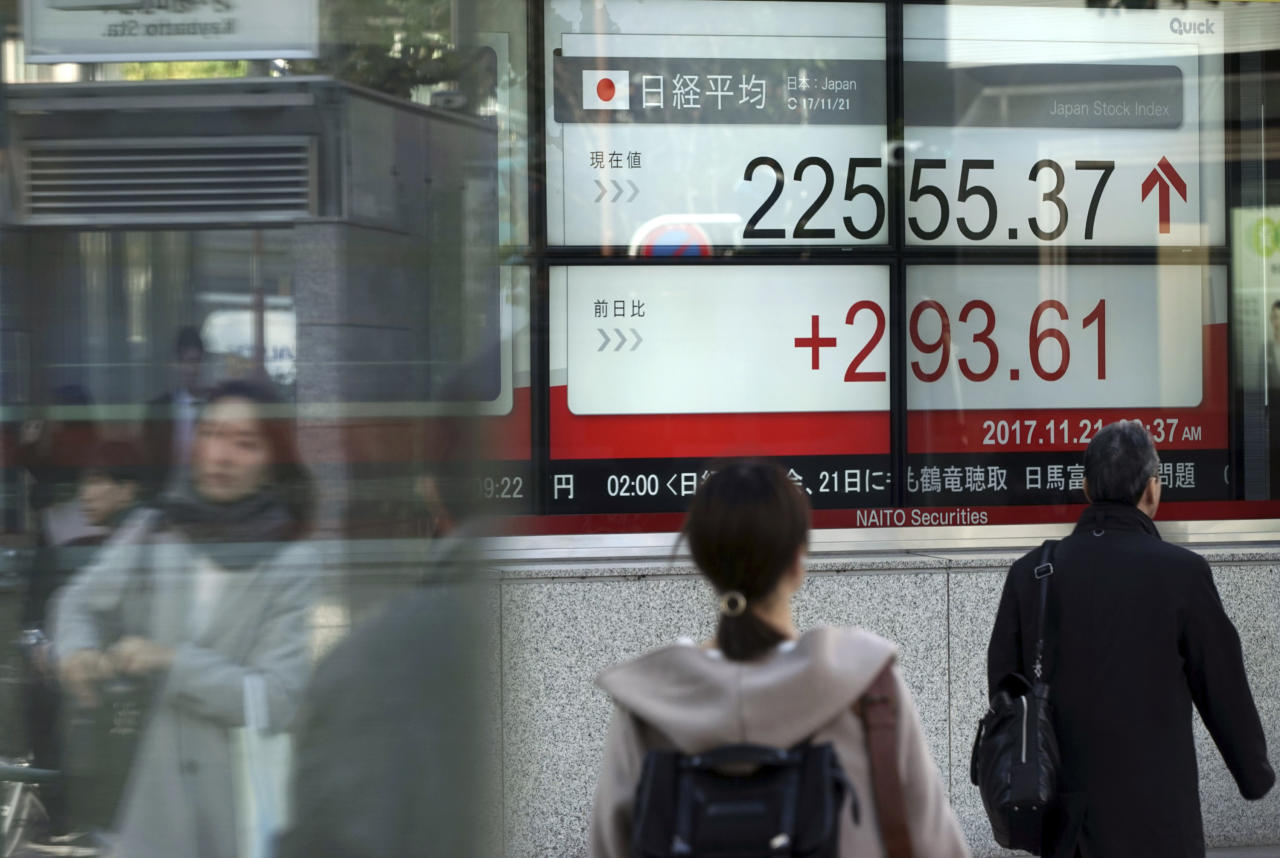 People walk past an electronic stock board showing Japan's Nikkei 225 index at a securities firm in Tokyo Tuesday, Nov. 21, 2017. Shares are higher in Asia after Wall Street regained lost ground overnight. Japan's benchmark rebounded as the yen held steady against the dollar. (AP Photo/Eugene Hoshiko)