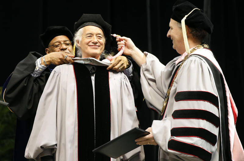 Former Led Zeppelin guitarist Jimmy Page, center, receives an honorary degree of Doctor of Music from Berklee College of Music President Roger Brown, right, and Provost Lawrence Simpson during the school's commencement in Boston, Saturday, May 10. 2014. (AP Photo/Winslow Townson)
