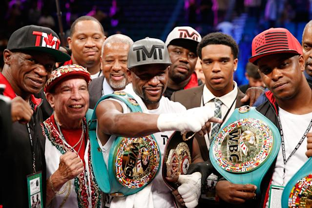 Rafael Garcia (second from left) celebrates with Floyd Mayweather in 2015 after Mayweather's victory over Andre Berto. (Getty Images)