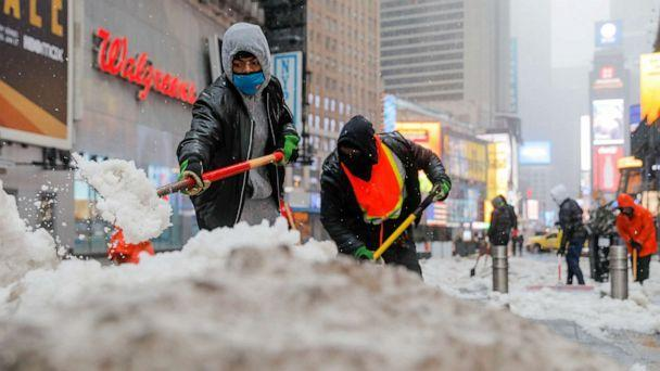 PHOTO: Workers shovel snow in Times Square as more severe weather arrives in Manhattan, Feb. 7, 2021. (Andrew Kelly/Reuters)