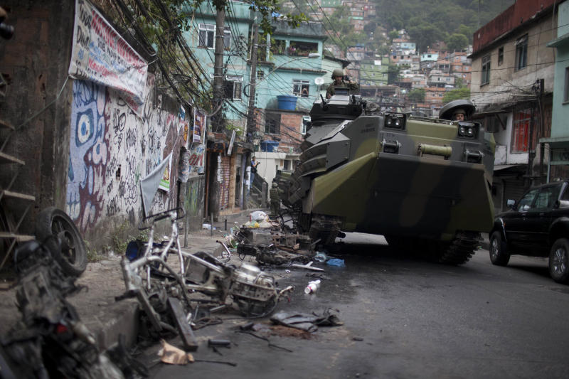 A Brazilian navy armored vehicle runs over motorcycles as it moves into Rocinha shantytown in Rio de Janeiro, Brazil, Sunday Nov.  13, 2011. Brazilian police backed by armored military vehicles have invaded Rio de Janeiro's biggest slum in what experts say it's the most important step yet in bringing security to Rio de Janeiro before it hosts the final matches of the 2014 World Cup and the 2016 Olympics.About 100,000 people live in Rocinha,  the biggest drug distribution point in Rio (AP Photo/Felipe Dana)