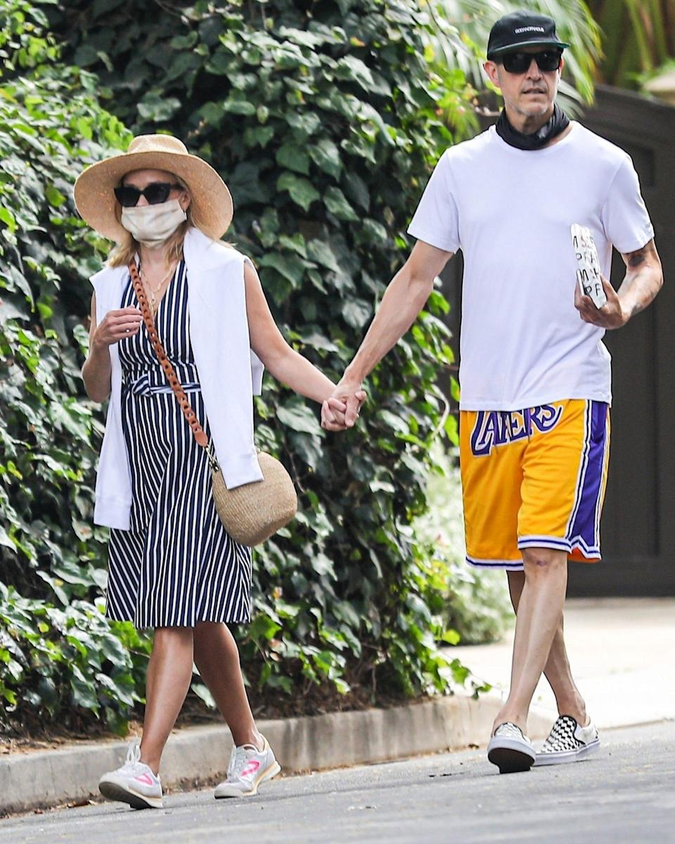 <p>Reese Witherspoon and husband Jim Toth hold hands while out for a stroll on Tuesday in Brentwood, California.</p>