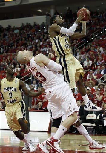 Georgia Tech's Brandon Reed drives to the basket as North Carolina State's Thomas de Thaey (13) defends during the first half of an NCAA college basketball game in Raleigh, N.C., Wednesday, Jan. 11, 2012. Georgia Tech's Mfon Udofia (0) looks on at rear. (AP Photo/Gerry Broome)