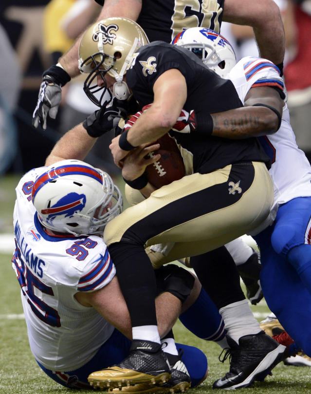 New Orleans Saints quarterback Drew Brees (9) is sacked by Buffalo Bills defensive tackle Kyle Williams (95) and strong safety Da'Norris Searcy 2during the first half of an NFL football game in New Orleans, Sunday, Oct. 27, 2013. (AP Photo/Bill Feig)