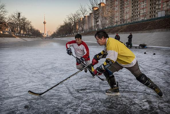 BEIJING, CHINA - DECEMBER 14- Chinese men play a game of pick-up ice hockey on a frozen canal on December 14, 2016 in Beijing, China. Though ice hockey is relatively new in China, winder interest in winter sport is growing and Beijing is set to host the 2022 Winter Olympics. (Photo by Kevin Frayer/Getty Images)