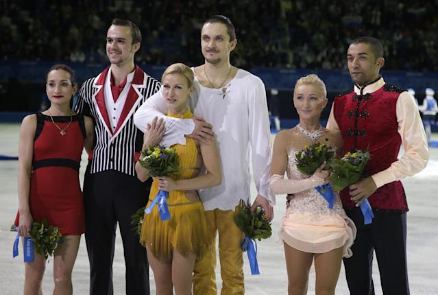 Tatiana Volosozhar and Maxim Trankov of Russia, centre, Ksenia Stolbova and Fedor Klimov of Russia, left, and Aliona Savchenko and Robin Szolkowy of Germany pose for photographs following the flower ceremony for the pairs free skate figure skating competition at the 2014 Winter Olympics, Wednesday, Feb. 12, 2014, in Sochi, Russia. Volosozhar and Trankov placed first, Stolboa and Klimov second, Savchenko and Szolkowy third. (AP Photo/Darron Cummings)