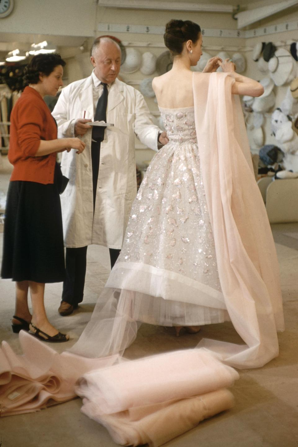 French fashion designer Christian Dior adjusts the dress on a model in his Paris salon, as part of preparations for his 1957 spring collection.