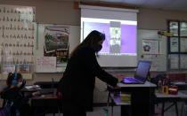 Wylona Rogers teaches students attending a class in-person as well as students attending virtually at Driggers Elementary School, Monday, Feb. 8, 2021, in San Antonio. After seeing two academic years thrown off course by the pandemic, school leaders around the country are planning for the possibility of more distance learning next fall at the start of yet another school year. (AP Photo/Eric Gay)