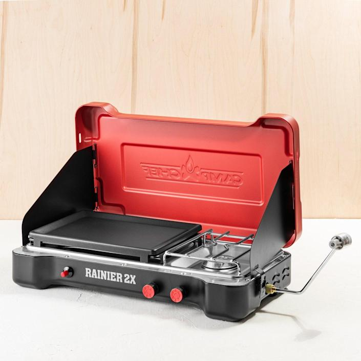 """This ultra-portable cook station offers a burner for boiling water as well as a griddle. <br> $180, Magnolia. <a href=""""https://shop.magnolia.com/products/camp-chef-rainier-cooking-system"""" rel=""""nofollow noopener"""" target=""""_blank"""" data-ylk=""""slk:Buy Now"""" class=""""link rapid-noclick-resp"""">Buy Now</a><br>"""