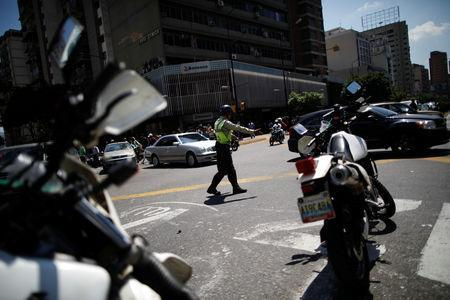 A police officer controls the traffic during a blackout in Caracas, Venezuela March 25, 2019. REUTERS/Carlos Garcia Rawlins