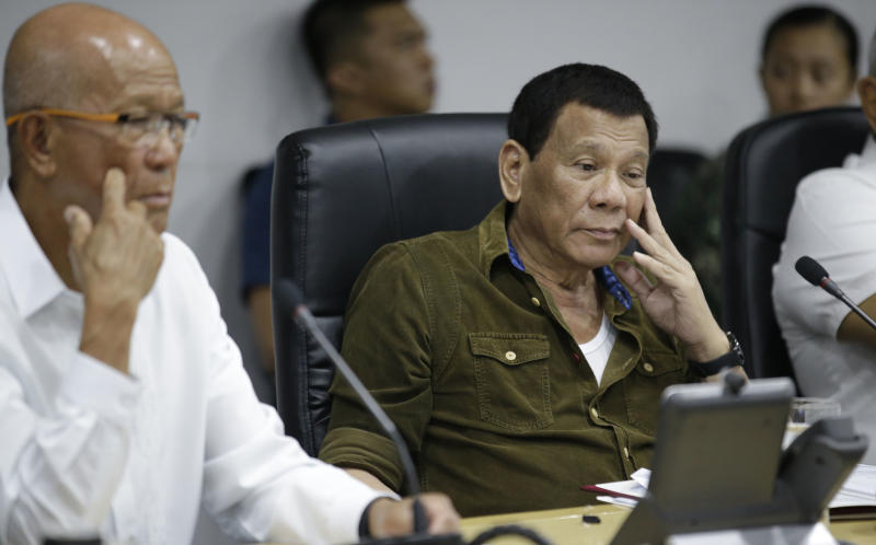 Philippine President Rodrigo Duterte, center, and Philippine Defense Secretary Delfin Lorenzana, left, attend a command conference on Typhoon Mangkhut, locally named Typhoon Ompong, at the National Disaster Risk Reduction and Management Council operations center in metropolitan Manila, Philippines on Thursday, Sept. 13, 2018. Philippine officials have begun evacuating thousands of people in the path of the most powerful typhoon this year, closing schools and readying bulldozers for landslides. (AP Photo/Aaron Favila)