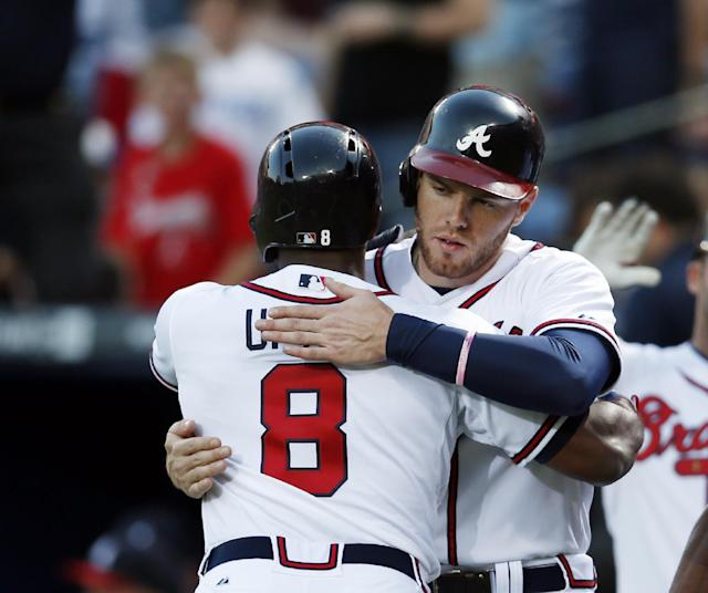 Atlanta Braves left fielder Justin Upton (8) gets a hug from first baseman Freddie Freeman (5) after hitting a three-run home run in the first inning of a baseball game against the Cincinnati Reds Friday, April , 25, 2014 in Atlanta. (AP Photo/John Bazemore)