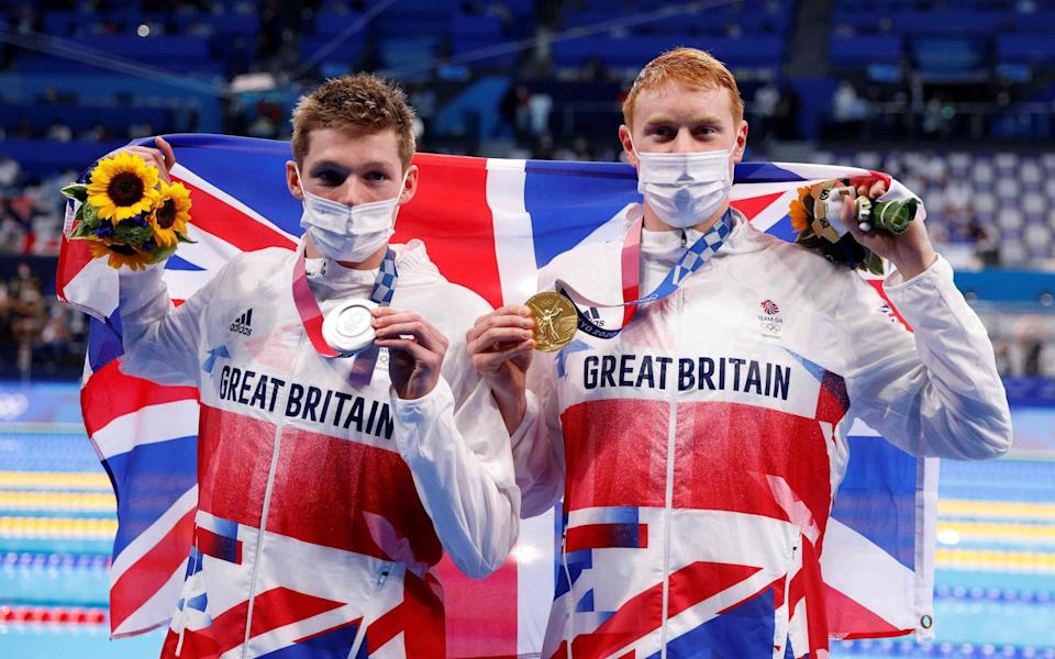 Team GB swimmers Duncan Scott, left, and Tom Dean, right, pose with their medals - Photo by Odd ANDERSEN / AFP