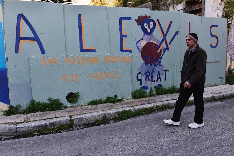 """A man walks past graffito in Athens on March 2, 2015 referring to Greek Prime Minister Alexis Tsipras, calling him the """"Great"""" (AFP Photo/Louisa Gouliamaki)"""