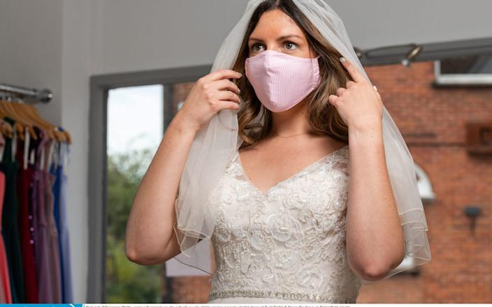 Georgina Watts wears a facemask as she adjusts a veil whilst wearing a Loulou bridal dress at Twirl Bridal & Dress Boutique - Jordan Pettit/Solent News & Photo Agency