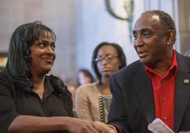 Johnny Rodgers, right, the 1972 Heisman Trophy winner, and girlfriend Reina Walls hold hands at a board of pardons hearing in Lincoln, Neb., Thursday, Nov. 14, 2013. Rodgers was granted a pardon from the state of Nebraska forty-three years after he and two other men held up a gas station following a night of drinking. (AP Photo/Nati Harnik)