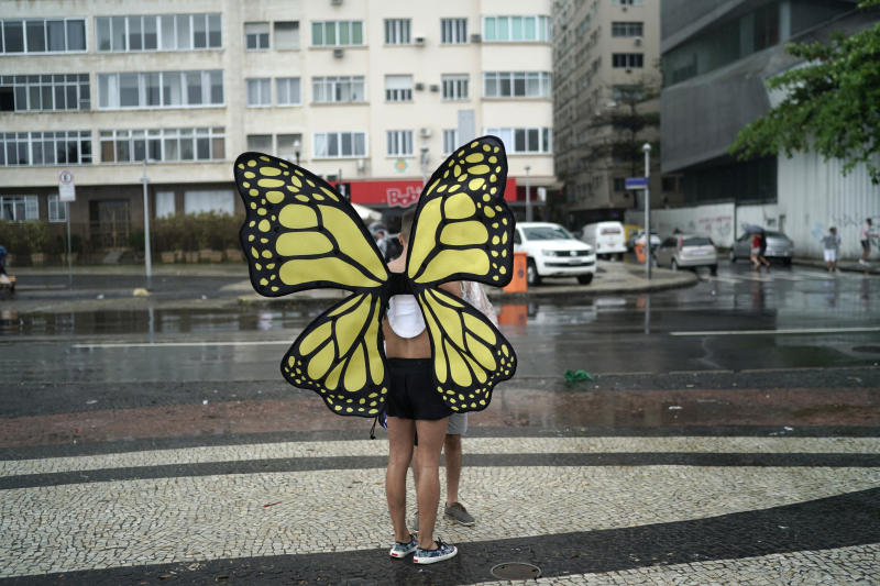 A person wearing butterfly wings stands on the sidelines of the annual gay pride parade along Copacabana beach in Rio de Janeiro, Brazil, Sunday, Sept. 22, 2019. (AP Photo/Leo Correa)