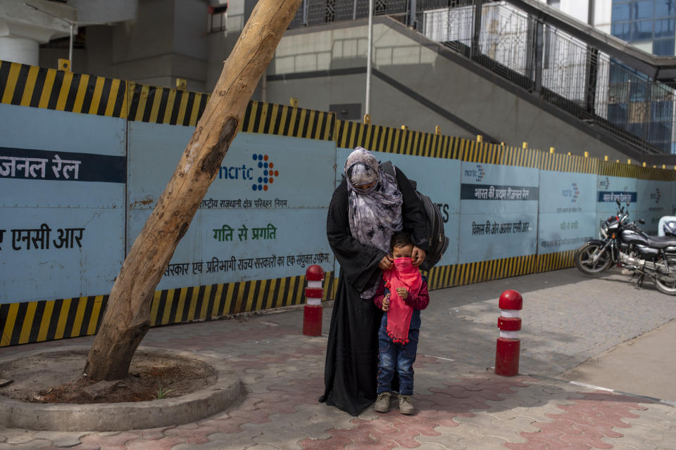 A woman covers the face of her child with a scarf at a bus terminal in New Delhi, India, Wednesday, March 24, 2021. (AP Photo/Altaf Qadri)